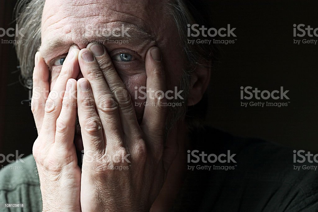 Caucasian man with hands over face showing his eyes  stock photo