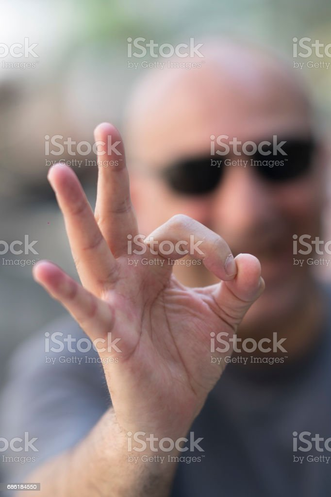 Caucasian man with sunglasses making ok sign at camera. Selective focus on foreground stock photo