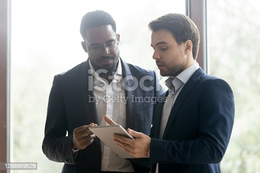 Diverse colleagues or business partners studying electronic document on tablet computer screen, smart caucasian agent offering life insurance, loan or rental of real estate to millenial african client