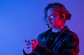 istock Caucasian man's portrait isolated on blue studio background in neon light 1266609925