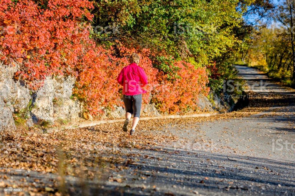 Caucasian mature woman running at sunset in autumn, Italy, Europe - Zbiór zdjęć royalty-free (55-59 lat)