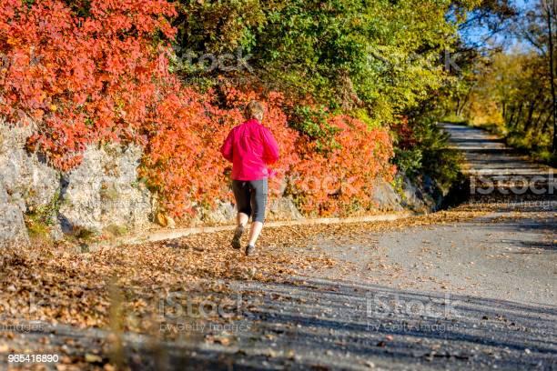 Kaukaska Dojrzała Kobieta Biegająca O Zachodzie Słońca Jesienią Włochy Europa - zdjęcia stockowe i więcej obrazów 55-59 lat