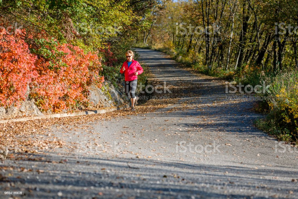 Caucasian mature woman running at sunset in autumn, Italy, Europe zbiór zdjęć royalty-free