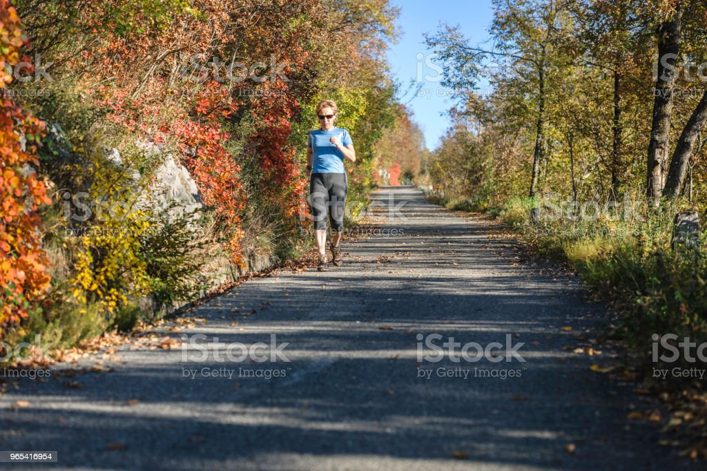 Caucasian mature woman running at sunset in autumn, Italy, Europe royalty-free stock photo