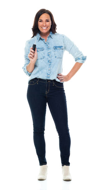 Caucasian mid adult women car salesperson standing in front of white background wearing shirt and holding key ring stock photo