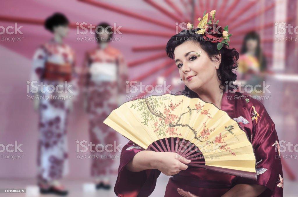 Caucasian model in kimono burgundy color with yellow fan stock photo