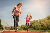 Caucasian mother and daughter jogging outdoors. Mother and daughter enjoying together.