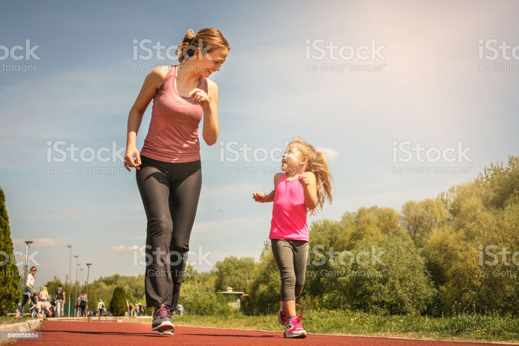 Caucasian mother and daughter jogging outdoors. Mother and daughter enjoying together. stock photo
