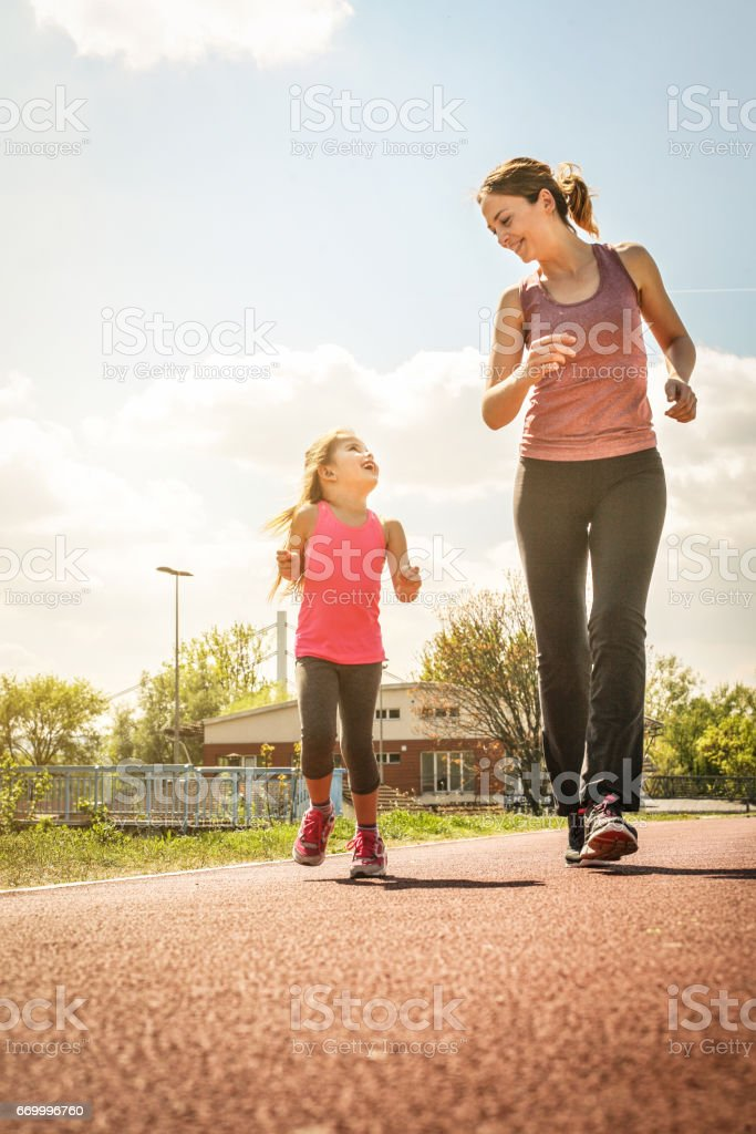 Caucasian mother and daughter jogging outdoors. stock photo