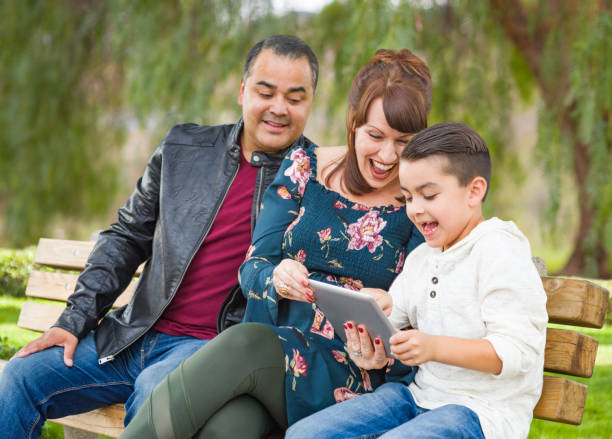 Caucasian Mother and Hispanic Father Using Computer Tablet With Mixed Race Son Outdoors stock photo