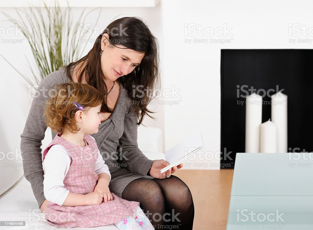 Caucasian Mother or Childminder And Toddler Reading On The Couch royalty-free stock photo