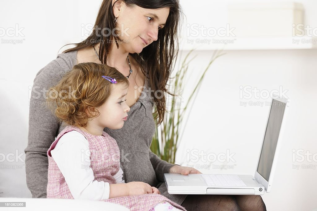 Caucasian Mother Using Laptop With Toddler stock photo