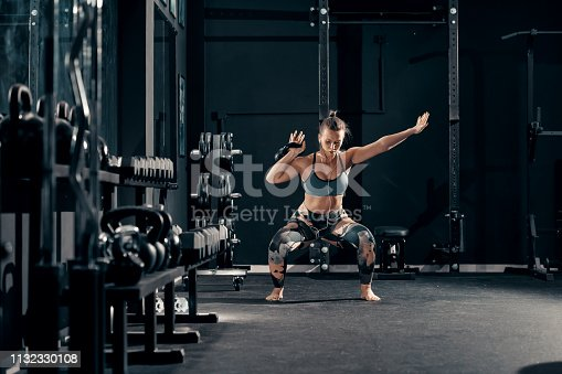 istock Caucasian muscular brunette with earphones in ears doing workouts with kettlebell in squat position. Night workout in gym concept. 1132330108