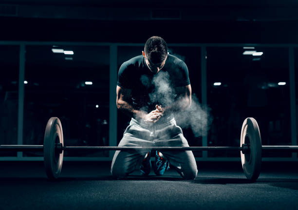 caucasian muscular man kneeling and clapping hands. in front of him barbell, in background mirror. gym interior, chalk all around. - pesistica foto e immagini stock