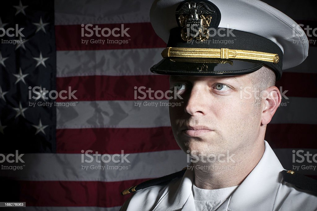 Caucasian Naval Officer In Uniform In Front of American Flag stock photo