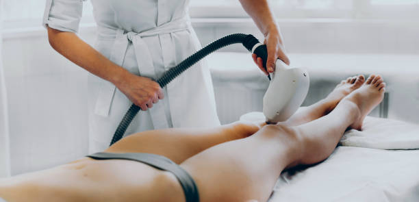 Caucasian salon worker is removing hair from the client's legs using modern apparatus stock photo