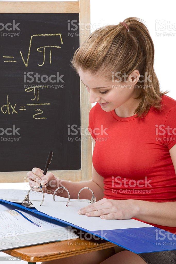 Caucasian schoolgirl by desk studying math exam royalty-free stock photo