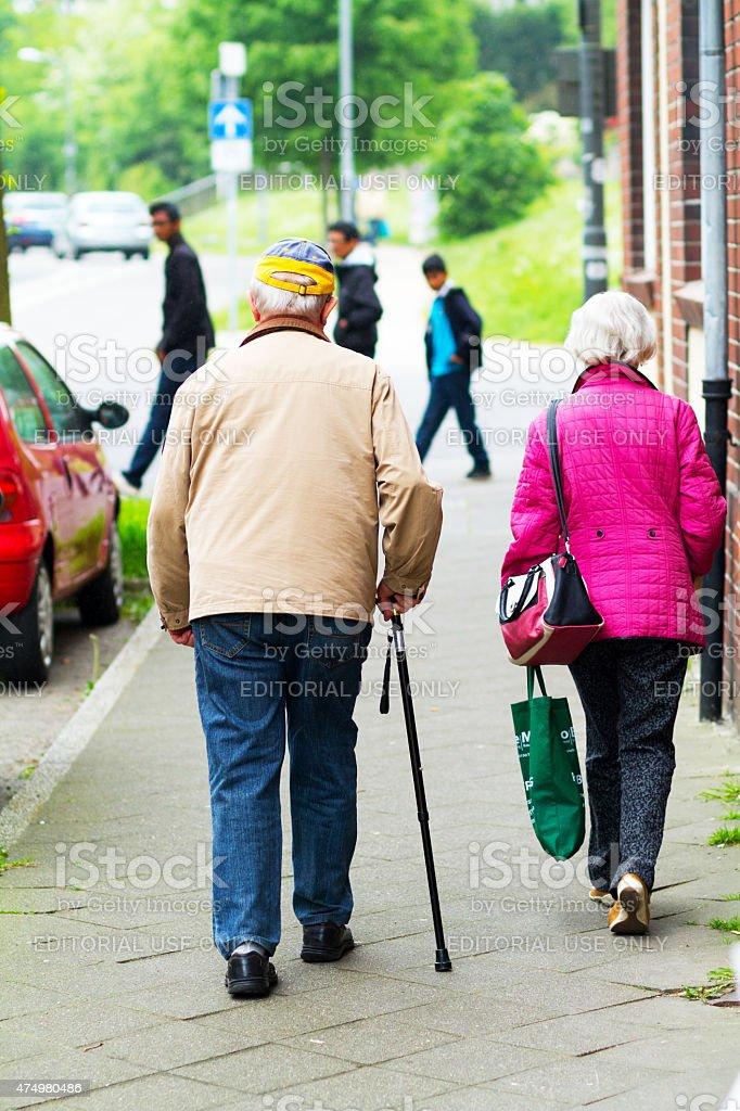 Caucasian senior couple walking along sidewalk stock photo