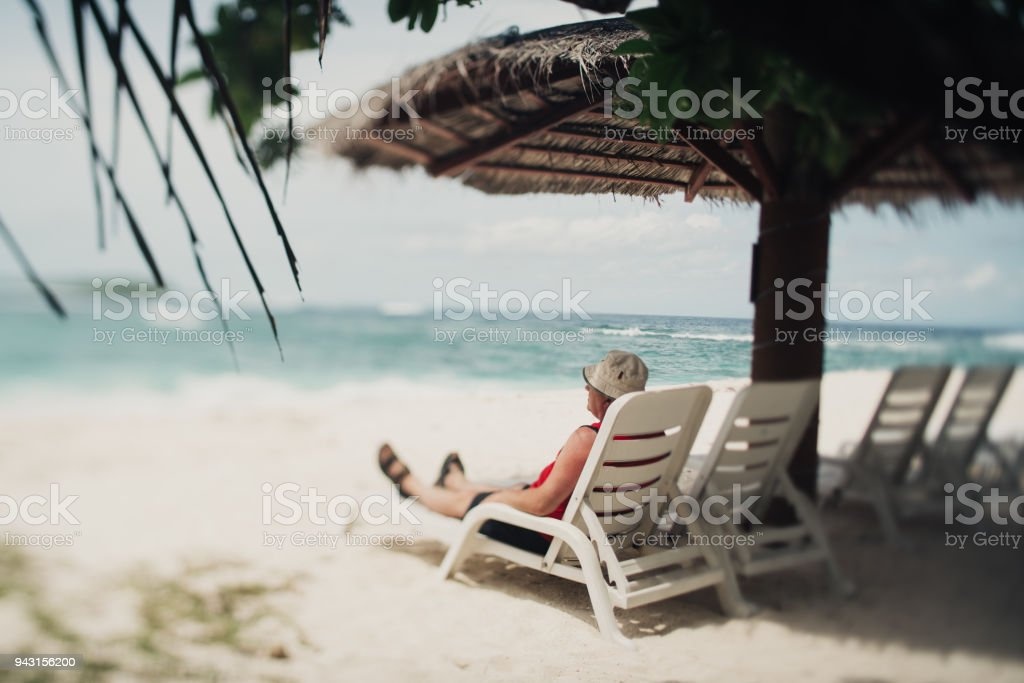 Caucasian senior tourist on the resort daybed next to sea stock photo