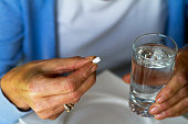 A caucasian senior woman is taking pill and is holding a glass with water. Pill is heart illness, cardiac and blood pressure.