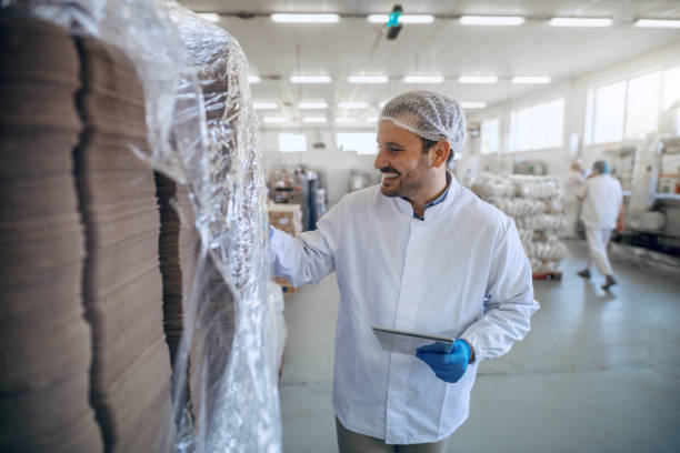Caucasian smiling employee in white sterile uniform using tablet in food factory. Caucasian smiling employee in white sterile uniform using tablet in food factory. hair net stock pictures, royalty-free photos & images