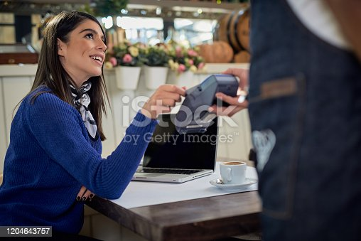 istock Caucasian smiling  woman paying bill with credit card while sitting in cafe. 1204643757