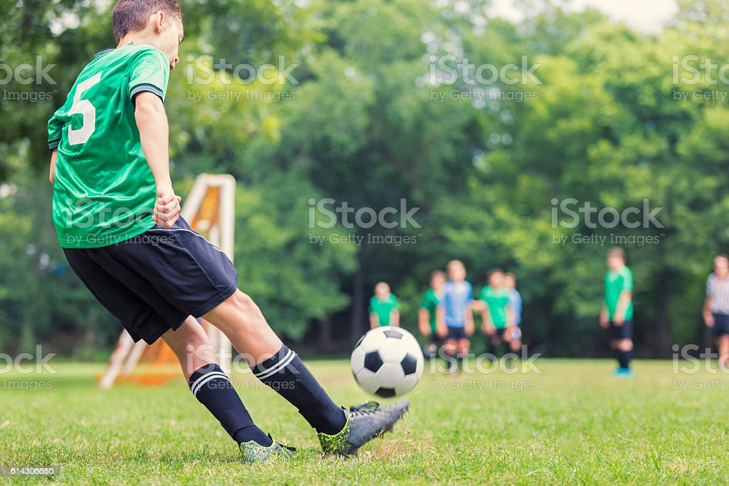 Caucasian soccer player kicks ball stock photo