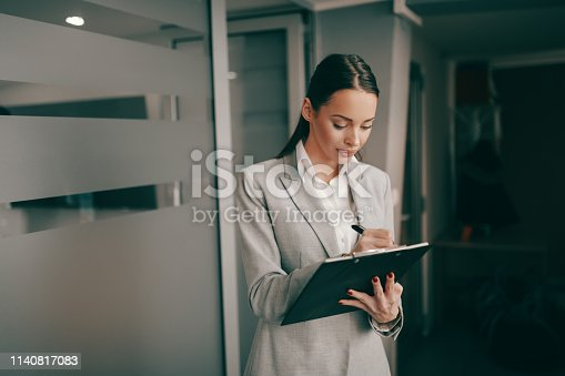 istock Caucasian successful businesswoman in formal wear standing at lobby in firm and writing on clipboard. Some people dream of success while others wake up and work. 1140817083