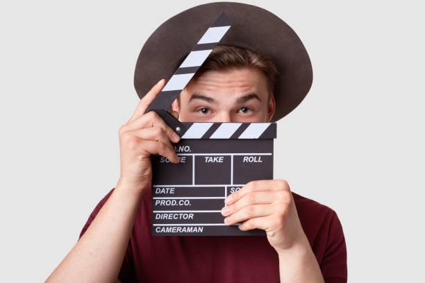 kaukasischer erfolgreicher männlicher produzent schaut durch oprnrd clapperboard, arbeitet an filmproduktion, trägt hut und lässiges t-shirt, isoliert über weißem hintergrund. filmwirtschaft und kinematographie - klappe hut stock-fotos und bilder