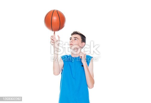Front view of aged 12-13 years old caucasian teenage boys basketball player spinning and holding basketball - ball and using sports ball
