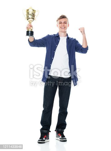 Front view of aged 16-17 years old with short hair caucasian teenage boys standing in front of white background wearing shirt who is successful and winning and showing award who is in first place and holding trophy