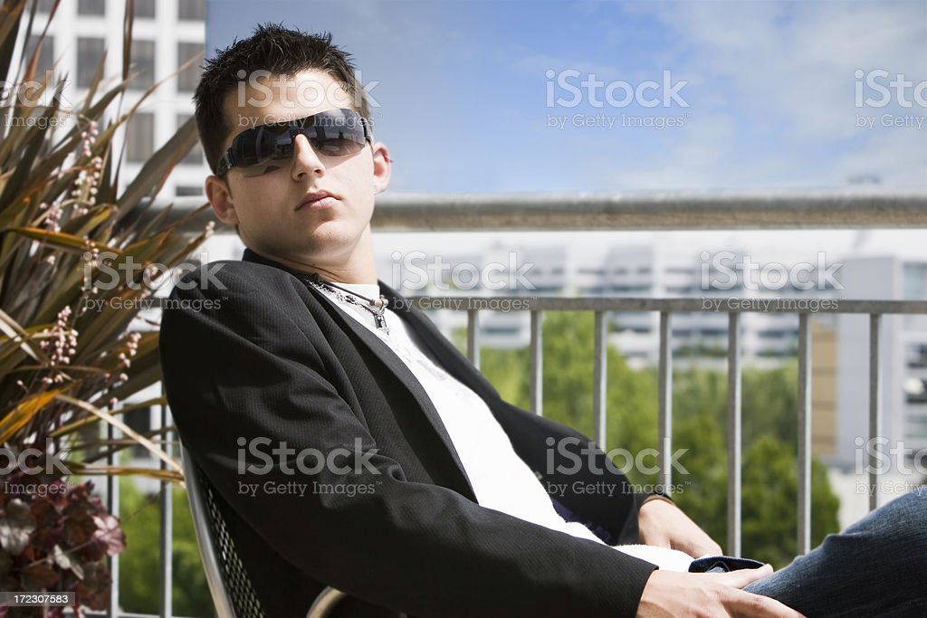 Caucasian Teenage Male Model on Rooftop with Sunglasses, Copy Space stock photo