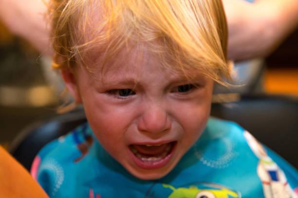 Kaukasische Kleinkind junge sitzt und weint während er bekommt seine Haare schneiden – Foto