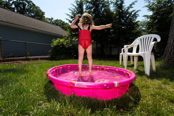 Kaukasische Kleinkind braune kurzhaarige Mädchen spielt In einem rosa Hinterhof Kiddie Pool während A heißen Sommertag – Foto