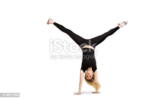 Caucasian woman does cartwheel gymnastics. Fitness girl in handstand isolated at white background. Gymnastics, yoga, fitness pose. Handstand and cartwheel in black clothes isolated at white