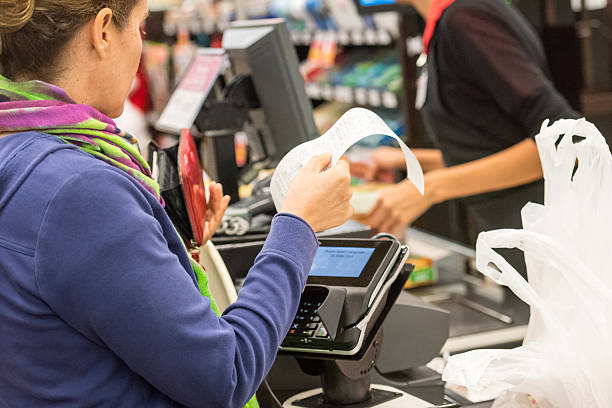 Caucasian woman electronic signing her bill Caucasian woman electronic signing her bill at the supermarket cash register stock pictures, royalty-free photos & images