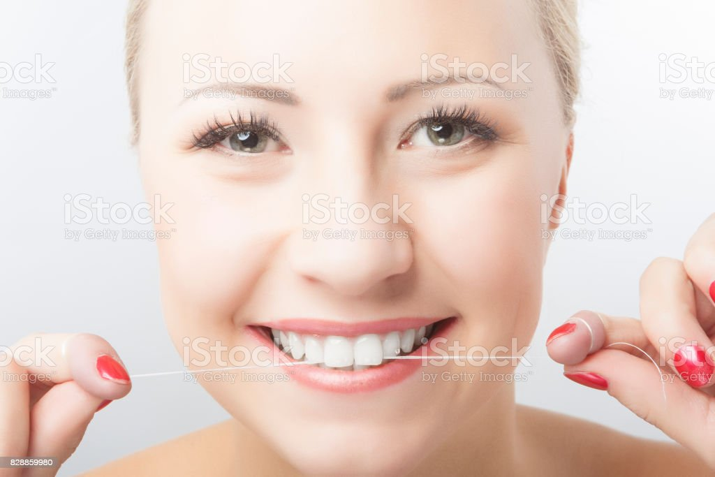 Caucasian Woman Flossing Teeth and Smiling. Dental Care and Oral Hygiene Concept. stock photo