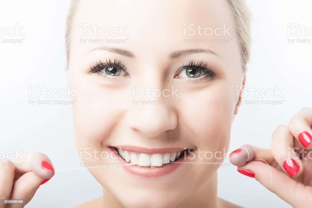 Caucasian Woman Flossing Teeth and Smiling. Dental Care and Oral Hygiene Concept stock photo