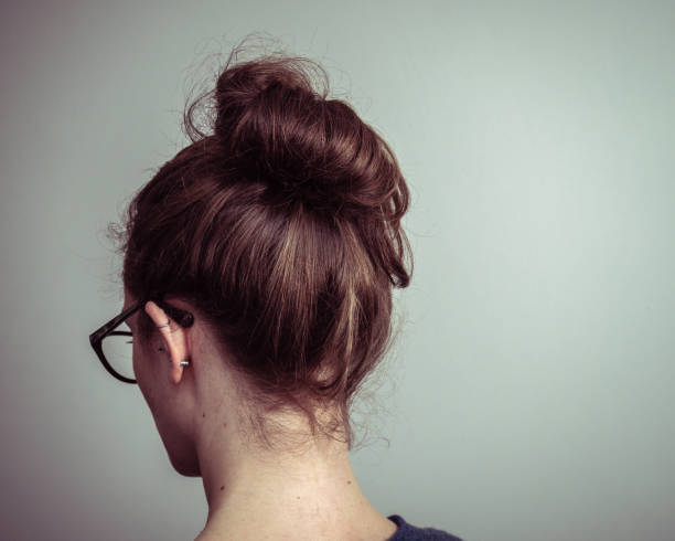 Caucasian woman from behind with brown hair in a ponytail stock photo