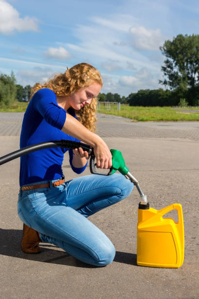 Caucasian woman fueling jerrycan with petrol stock photo
