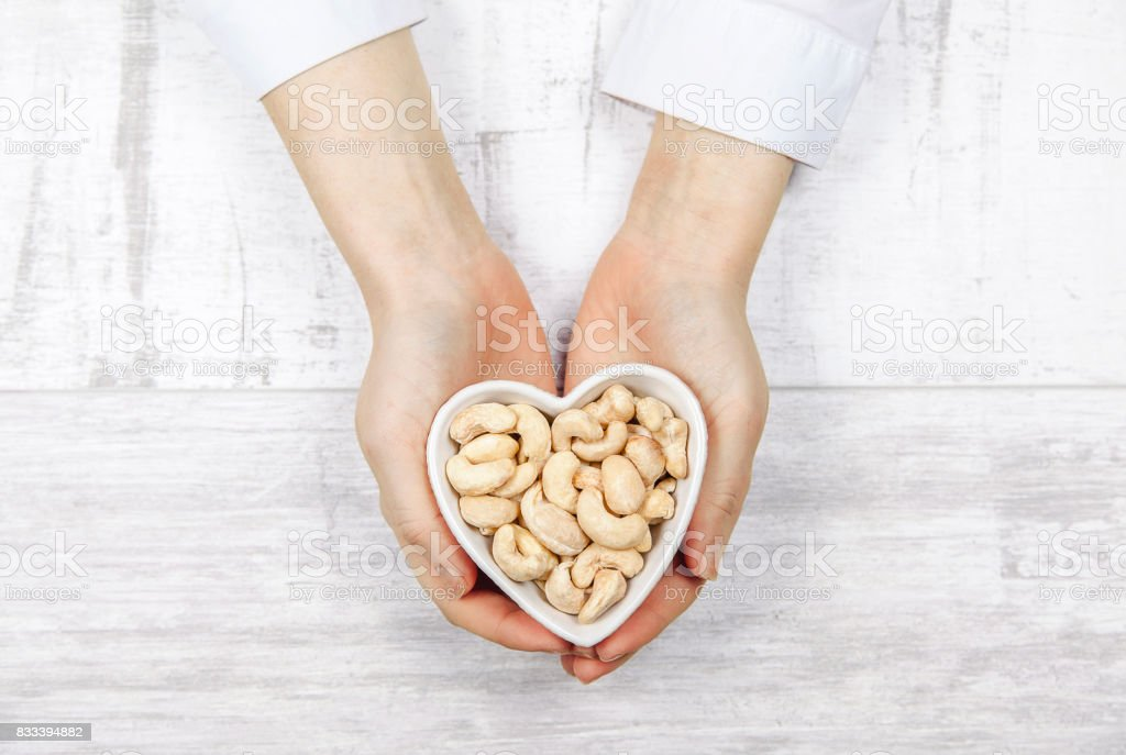Caucasian woman holding cashew nuts in a heart shaped - foto stock