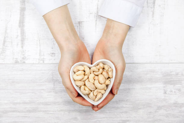 caucasian woman holding cashew nuts in a heart shaped - cashew stock photos and pictures