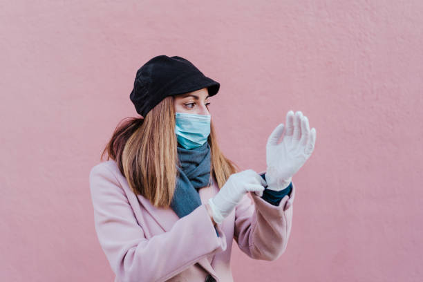 caucasian woman in the street wearing protective gloves and using mobile phone. corona virus concept stock photo