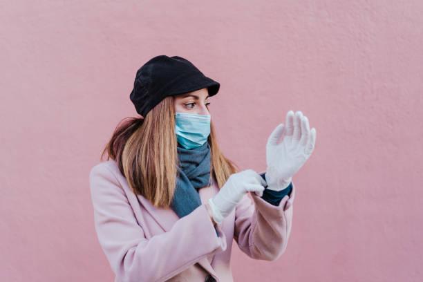 mujer caucásica en la calle usando guantes de protección y usando el teléfono móvil. concepto de virus corona - foto de stock