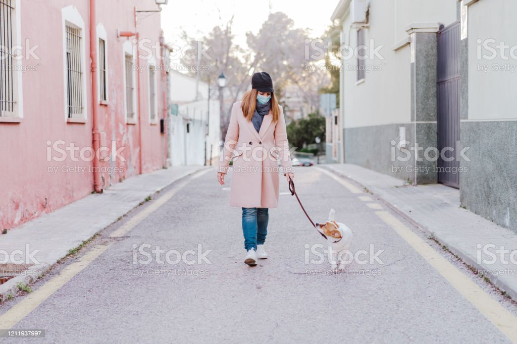 Kaukasische vrouw in de straat die beschermend masker draagt en met haar hond loopt. corona virus concept - Royalty-free Ademhalingsstelsel Stockfoto