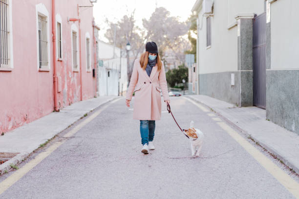 caucasian woman in the street wearing protective mask and walking with her dog. corona virus concept stock photo