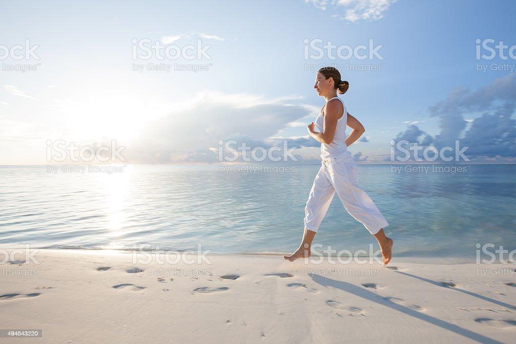 Caucasian woman jogging at seashore stock photo