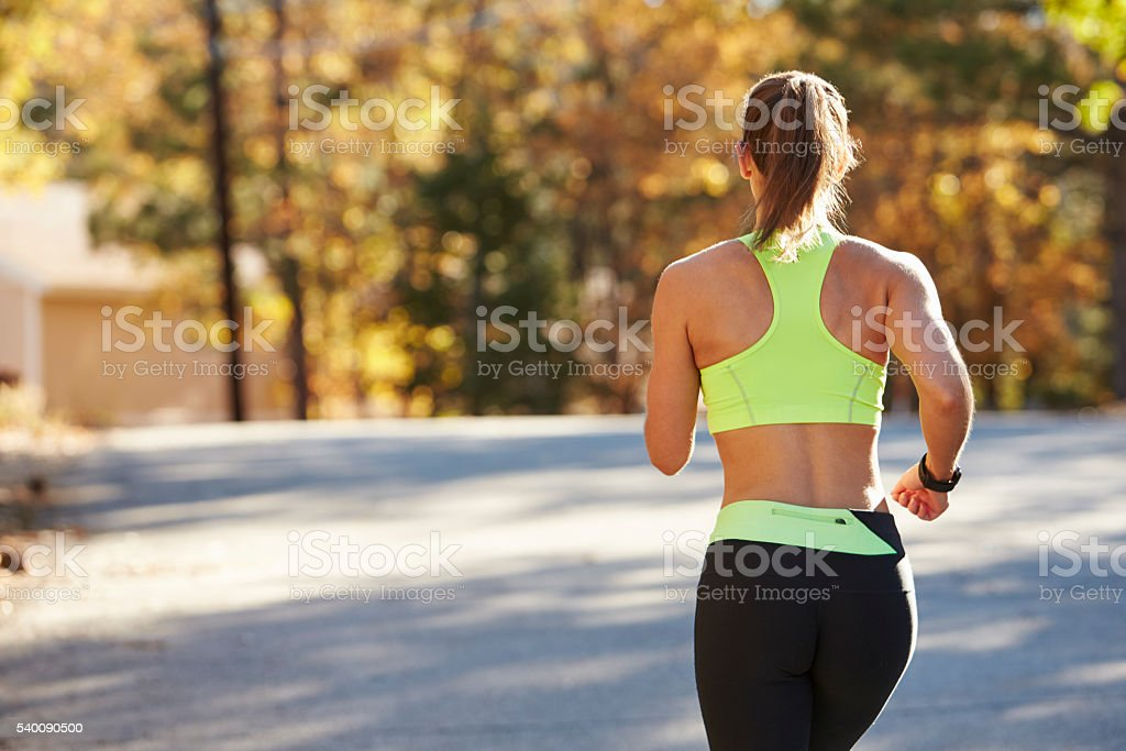 Caucasian woman jogging on country road, back view close up royalty-free stock photo