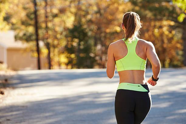 caucasien femme faire du jogging sur la route de campagne, gros plan, vue de derrière - brassière de sport photos et images de collection