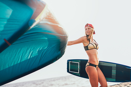 Caucasian woman kitesurfer walking on the beach